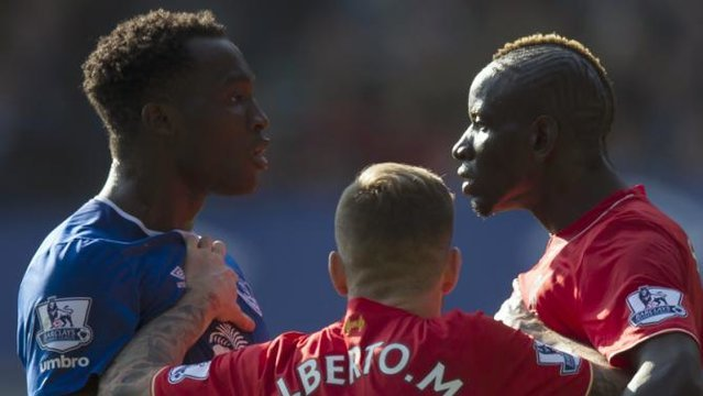 Everton's Romelu Lukaku, left, and Liverpool's Mamadou Sakho, right, are separated by Liverpool's Alberto Moreno after a confrontation during the English Premier League soccer match between Everton and Liverpool at Goodison Park Stadium, Liverpool, England, Sunday Oct. 4, 2015. (AP Photo/Jon Super)